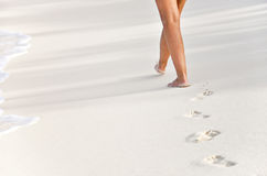 Woman walking the beach Royalty Free Stock Images