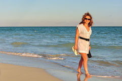 Woman walking on the beach Royalty Free Stock Images