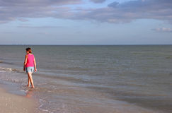 Woman walking on beach Royalty Free Stock Photos