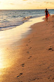 Woman walking on beach. Woman walking on tropical beach at sunrise Stock Photography