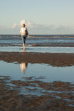 Woman walking on beach. Woman walking alone on beach in late afternoon Stock Photo
