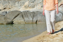 Woman walking on the beach Stock Image