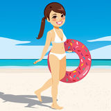 Woman Walking Beach. Beautiful young woman walking on the beach with doughnut inflatable wearing white bikini Stock Photos