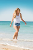Young woman on the beach. Hot blonde woman slowly walking on the beach. Feet in the water of the sea Royalty Free Stock Photo