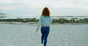 Woman walking on beach at dusk 4k. Rear view of woman walking on beach at dusk 4k stock footage
