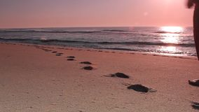 Woman walking on beach leaving foot prints stock video