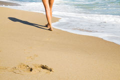 Woman walking on the beach. Woman walking on beach leaving footprints in the golden sand royalty free stock images