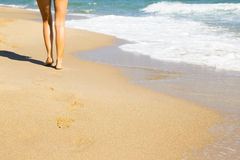 Woman walking on the beach. Woman walking on beach leaving footprints in the golden sand stock images