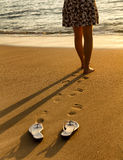 Woman walking on beach into ocean Stock Photos
