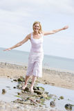 Woman walking on beach path smiling Stock Photo