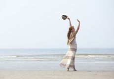 Woman walking on the beach with raised arms Royalty Free Stock Photos