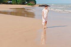 Woman walking on the beach sand Stock Photo