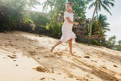 Woman walking on the beach sand royalty free stock images