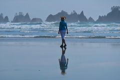 Woman walking on beach with scenic views of sea stacks. stock photo
