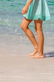 Woman walking. Sexy woman dressed with green skirt walking bare foot on the beach shore. Closeup of her tanned naked shaved legs. Closeup detail of female feet Royalty Free Stock Photo