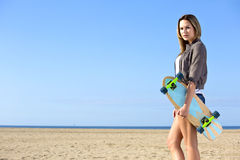Woman walking on a beach with a skateboard Royalty Free Stock Photography