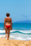 Woman Walking on Beach Stock Images