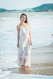 Woman walking on beach in summer. Happy multiracial Asian girl going to sea. Woman walking on beach in summer. Beautiful happy multiracial Asian girl in white Stock Photo
