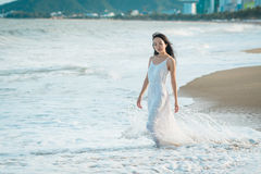 Woman walking on beach in summer. Happy multiracial Asian girl going to sea. Woman walking on beach in summer. Beautiful happy multiracial Asian girl in white Stock Photos