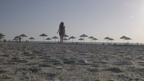 Woman Walking at the Beach. Summer vacation scene. Empty beach with lots of sun umbrella silhouettes on the ocean coast. Fit slim figure of a young beautiful stock video