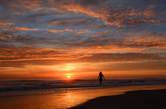 Woman walking on the beach at sunrise. Royalty Free Stock Photos