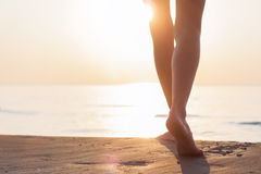 Woman walking on the beach Stock Photos