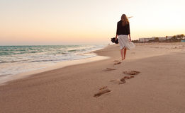 Woman walking beach sunset. Woman walking away beach sand sunset sea ocean water summer vacation
