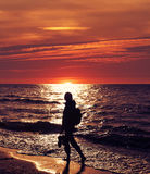 Woman walking on the beach at sunset, backlight. Royalty Free Stock Image