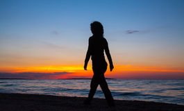 Woman walking on the beach at sunset Royalty Free Stock Photo