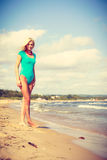 Woman walking on beach wearing swimsuit. Being trendy and fashionable during summer vacation concept. Blonde slim attractive woman walking on beach wearing blue Stock Photo