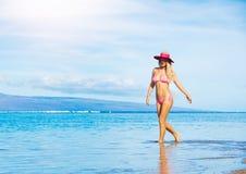 Woman walking on the beach Stock Photos