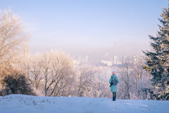 Woman walking in beautiful winter park with cityscape landscape Royalty Free Stock Image