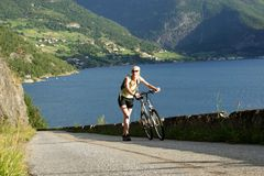 Woman walking with bicycle in the mountains. Sporty woman walking with bike in thhe mountains stock photos