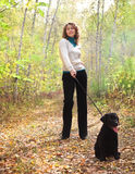 Woman walking with black labrador retriever puppy Stock Images