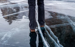 Woman walking on blue cracked ice of frozen lake Baikal. Ice with reflection Stock Images