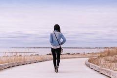 A woman walking on a boardwalk Stock Photography
