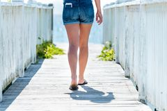 Woman walking on boardwalk out to ocean. On a bright day Stock Image