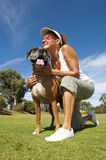 Woman walking boxer bulldog in park Royalty Free Stock Photo