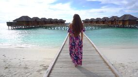 Woman walking on bridge on beach with transparent water of ocean in Maldives. Woman walking on bridge on beach with pure transparent water of ocean in Maldives stock video