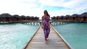 Woman walking on bridge on beach with transparent water of ocean in Maldives. Woman walking on bridge on beach with pure transparent water of ocean in Maldives stock video footage
