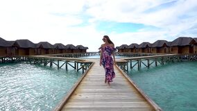 Woman walking on bridge on beach with transparent water of ocean in Maldives. Woman walking on bridge on beach with pure transparent water of ocean in Maldives stock footage