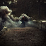 Woman walking on the bridge in heavy black smoke. Like a witch Royalty Free Stock Photos