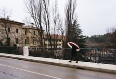 A woman walking by the bridge in small town. Woman walking by the bridge in cuenca, spain with red umbrella. cuenca, february 2017 stock photography