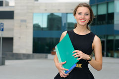 Woman walking on business district with folders Royalty Free Stock Photography