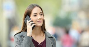 Woman walking and calling on phone in the street. Relaxed woman walking and calling on phone in the street