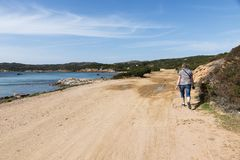 Woman walking on caprera island. Caprera,Italy,07-april-2018:Adult womand walking along the roads of Caprera island, this island belongs to the maddalena Royalty Free Stock Images