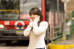Woman walking on the city street covering her ears Royalty Free Stock Image
