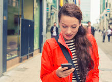 Woman walking on a city street and using her mobile phone stock photo