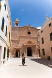 Woman walking in Ciutadella city in Minorca. Woman walking in street in old town of Ciutadella city, with facade of Church of Roser behind, in Menorca, Balearic Stock Image