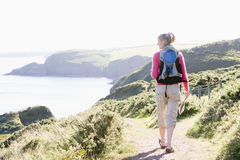 Woman walking on cliffside path Royalty Free Stock Photo